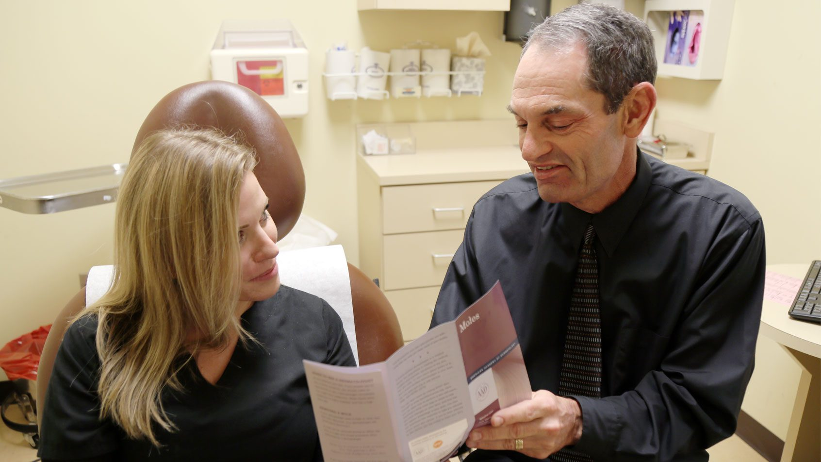 Board certified dermatologist, Dr. Alan Parks, gives information to a patient